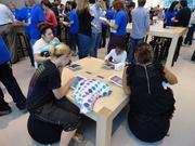 Customers could sit or stand at tables throughout the store to test drive Apple's gadgets.