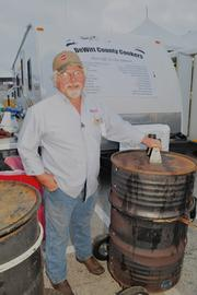 Bobby Daw, of the Shelby County cookers, shows off the team's unique barbecue pits that were transformed from old smoking barrels.
