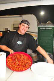 """""""Capt. Up"""" from the grand champion prize winning Motley Que Crew shows off some of the team's spicy crawfish."""