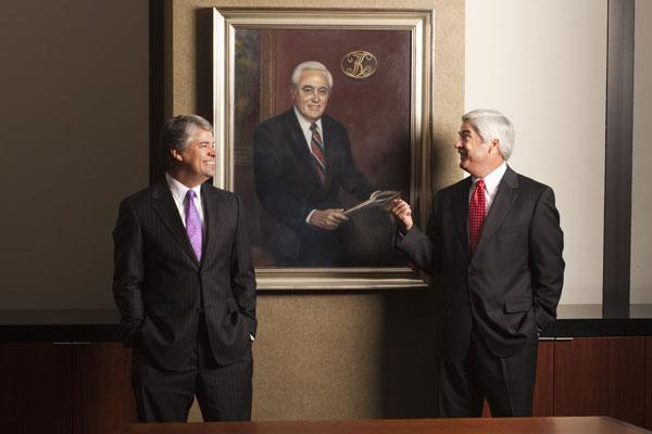 Drew Kanaly, CEO and chairman, left, and Jeff Kanaly, vice chairman and  CFO, stand in front of a portrait of their father, E. Deane Kanaly, who  founded the Kanaly Trust LTA wealth management firm almost 30 years ago.