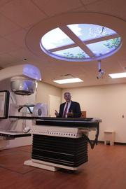 Radiation oncologist Mark Bonnen stands next to an Elekta radiation treatment machine. The department has two other machines similar to this one.