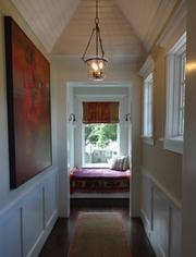 A view down the upstairs hallway toward the rear of the home and another reading nook.