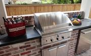The outdoor rear porch has a built-in gas grill and cooking area.