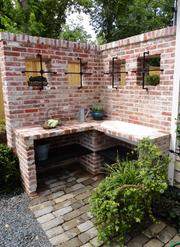 The reclaimed brick work area in the rear garden. A rusted antique metal chair, bottom right, has been turned into a vegetation showpiece.