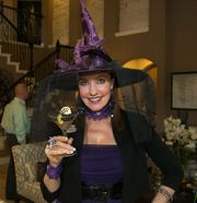 """Karen Nickell, sales manager with D.R. Horton, staffed the builder's model home in Woodforest recently wearing """"witchy"""" attire. She is holding a """"graveyard shooter"""" dessert that was served to Realtors visiting the new model that day."""