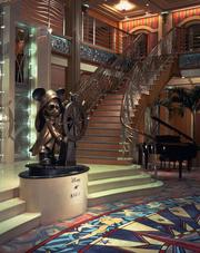 The three-deck atrium lobby on the Disney Magic is designed with Art Deco-inspired details and features bronze statue of Helmsman Mickey.