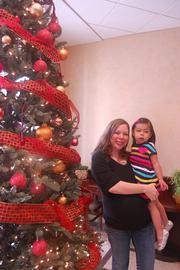 David Weekley Homes hosted a holiday open house with a brunch buffet, ornament making, a hot chocolate bar and photos with Santa. Web Coordinator Margie Oviedo holds her daughter, Camilla, who enjoyed making an ornament and meeting Santa.