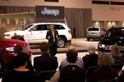 Jeep Brand Director Jim Morrison addresses media members, flanked by the 2013 models of the Grand Cherokee (left and center) and Compass.