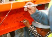 Dignitaries and other officials present at the stadium ceremony signed the steel girder painted in the Houston Dynamo's familiar orange hue before it was lifted into place.