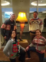 """TopSpot Internet Marketing decorated its office with a """"Santa's Workshop"""" sign, the lamp from """"A Christmas Story"""" and more. (Clockwise from top left) Jack Glauser, Thomas Morrow, Julia Alaniz and Yvonne Duong show off their tacky Christmas sweaters."""