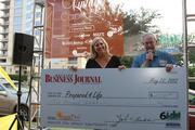 Julie Eberly accepts a check for nonprofit Prepared4Life from John Beddow of the Houston Business Journal. Vintage Capitalism was a fundraiser for Prepared4Life's communitywide initiative Lemonade Day.