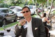 Jim Streets of PKF Texas enjoys a cigar on The Tasting Room's patio.