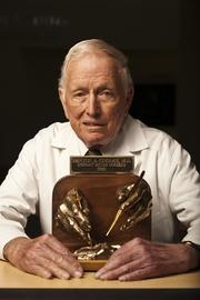 Dr. Denton A. Cooley at the Texas Heart Institute, with a casting showcasing his hands during an open heart operation.