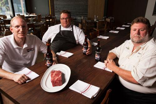 From left, Brock Wagner, founder of Saint Arnold Brewing Co.; Chris Shepherd, owner of Underbelly, and Gene Terry, owner of Texas T Kobe beef ranch, with bottles of Endeavour beer — and a cut of beef from Terry's herd.
