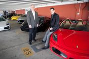 Smith and Prejean pose with some of the club's high-end sports cars.