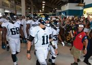 Jaguars' quarterback Blaine Gabbert (center) and running back Maurice Jones-Drew (right) lead the team through the crowd.