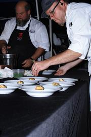 Chef Tom Gray (right) putting the finishing touches on Chef Ferri's Seven Fishes dish.
