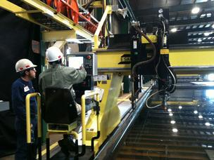 BAE workers operate a plasma cutter used to cut the steel for two oil platform supply vessels at the BAE facility on Heckscher Drive.