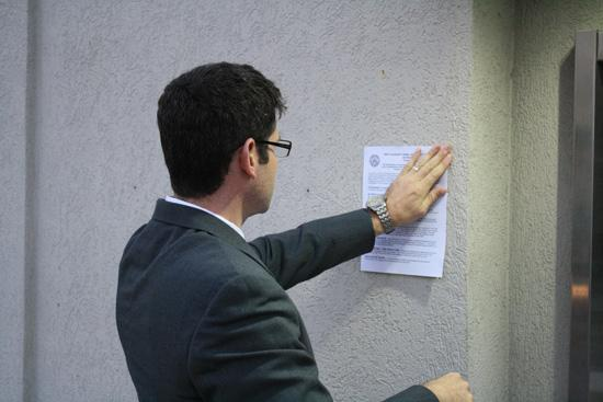 An FDIC employee puts a notice on the wall of the First Guaranty Bank. The FDIC failed the bank Jan. 27 at 5 p.m.