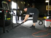 Lee Bussen vacuuming water out of the carpet at Jack Rabbits.