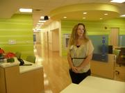Registered nurse Carie Murphy stands in the receptionist area of the children's hematology and oncology floor of the new J. Wayne and Delores Barr Weaver Tower.