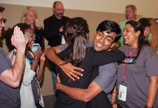 Karthik Kadirvel hugs wife Sona Muthuvijayan after they took top prize at the second Jacksonville Startup Weekend for creating a music app.