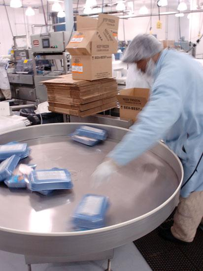 A worker at Beaver Street Fisheries processes packages of frozen tilapia for shipping