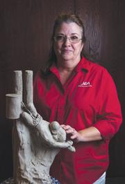 """Karen Perkins of JEA and her sculpture of Rocco Moribito's Pulitzer Prize winning photograph, """"Kiss of Life."""""""