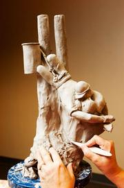 """Karen Perkins of JEA and her sculpture of Rocco Morabito's Pulitzer Prize winning photograph,""""Kiss of Life."""""""