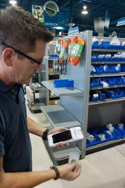Chad Kluko, vice president of HomeParts, demonstrates a handheld payment system.