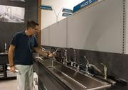 Chad Kluko, vice president of HomeParts, demonstrates the faucet bar at the new store in Jacksonville Beach. Shoppers will be able to try out faucets before purchase.
