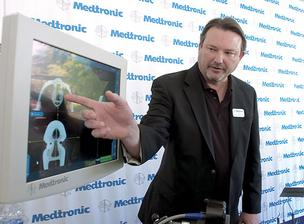 Scott Carpenter of Medtronic explains how one of its medical devices works after a groundbreaking ceremony for a 75,000-square-foot facility that will create 175 new jobs by the end of 2015.