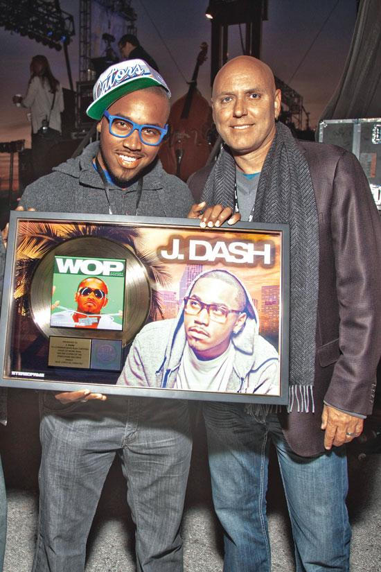 """Ken Underwood, founder and CEO of Stereofame, poses with Stereofame artist J. Dash after the artist was presented with his first gold record for his single """"WOP."""""""