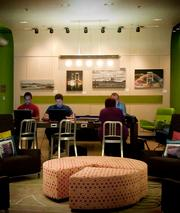 Aloft Tapestry Park guests use their laptop computers during the hotel's happy hour.