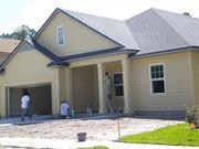 A painting crew puts the finishing touches on a home under construction at Greenland Chase off Greenland Road.