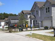 A crew lays down sod at a home under construction at Greenland Chase on the Southside.