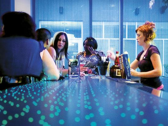 The $9.3 million Aloft Hotel in Tapestry Park opened Jan. 13. Customers gather around the bar during the hotel's happy hour.