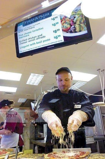 Winn-Dixie cook Brian Blackburn prepares a pizza its first transformational store on County Road 210.