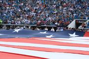 Members of various branches of the military waving the flag during the national anthem.