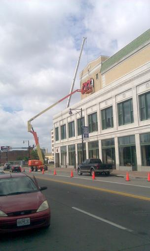 Workers tear down the AMC signs from the Mainstreet 6 theater in downtown Kansas City after the joint venture to run the facility falls apart.