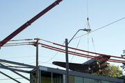 A crane starts to lift the DC-3 up and over The Roasterie's plant.