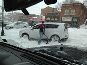 A good Samaritan helps dig this sport-utility vehicle out from an intersection in downtown Parkville.