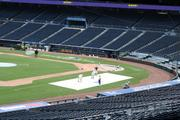 Kauffman Stadium workers paint the All-Star Game logo along the third base line on Tuesday.