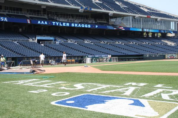 Workers at Kauffman Stadium water the grass on the field inpreparation for the upcoming All-Star Game.