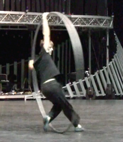 A performer uses a Cyr Wheel to spin and turn across the stage.