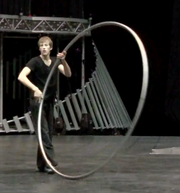 "A performer uses a ""Cyr Wheel"" to spin and turn across the stage."