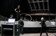 "The Cirque's production crew directs Ghislain Ramage on how to become a ""human spoke"" by using the Cyr Wheel."