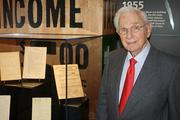 Co-founder Henry Bloch stands next to his first personal tax filing, encased in a transparent box in the archive.