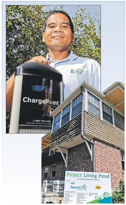 """Roland Maliwat, Kansas City Power & Light Co.'s product manager for mass markets, with an electric """"gas station"""" ready to charge cars at the Clean Cities Living Proof concept home at 917 Emanuel Cleaver Blvd."""