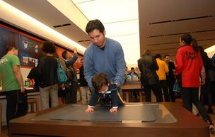 A child and his father try out the Microsoft Surface at the November grand opening of the 14th Microsoft Store at Tysons Corner Center in McLean, Va. One of those stores will open soon at Oak Park Mall in Overland Park.